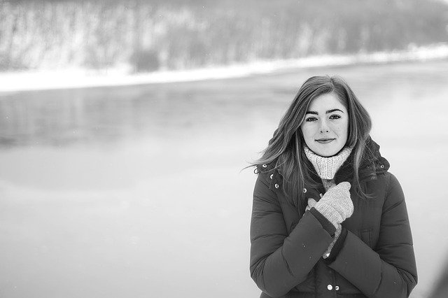 dívka v zimní bundě u vody
