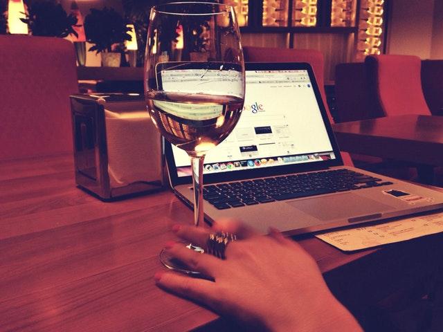 lidé rádi vybírají zboží v klidu svého domova a musí je stránky zaujmout – žena se sklenkou vína u PC
