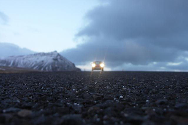 pohled z vozovky, v dáli jedoucí automobil, svítí mu světla, kolem jsou hory a velké modré mraky