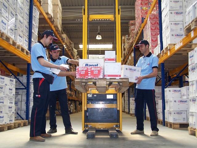tři chlapi u vysokozdvižného vozíku přebírají krabice ve skladu, kde je plno dalších krabic na vysokých regálech