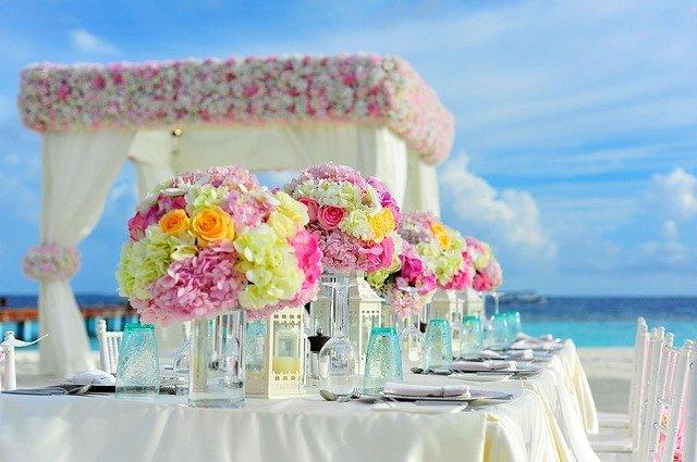 prostřený svatební stůl někde na pláži, výrazné květiny na stole, prostřeno na bílo