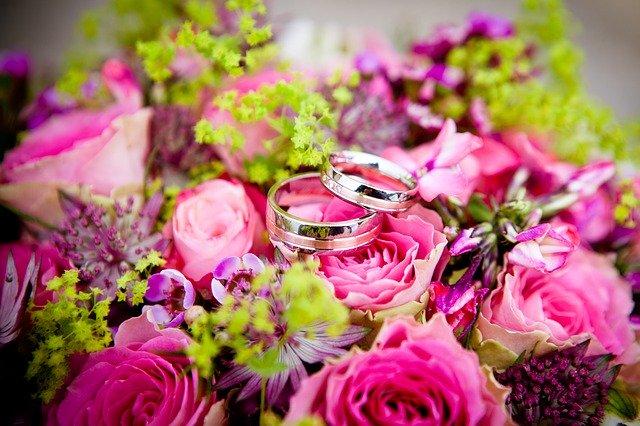 kytice z růžových květin a na ní jsou položené dva snubní prsteny
