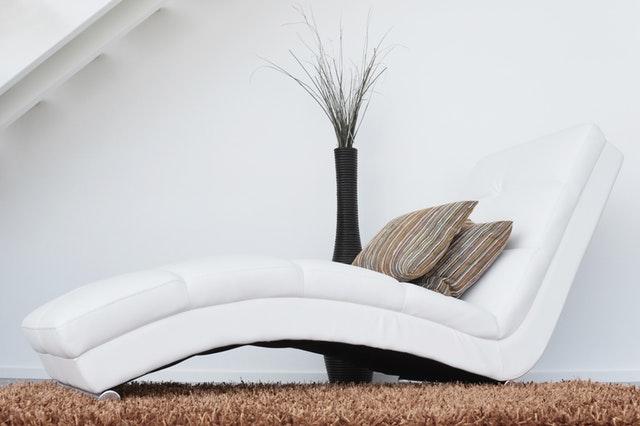 bílá pohovka, polštáře, hnědý koberec