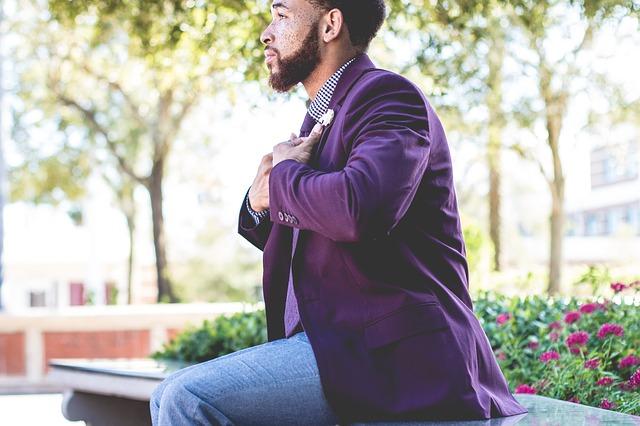 muž ve fialovém saku sedící na lavičce v parku
