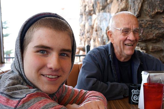 mladý kluk se dívá do objektivu, sedí u stolu, vedle něj je starý pán v bundě a směje se