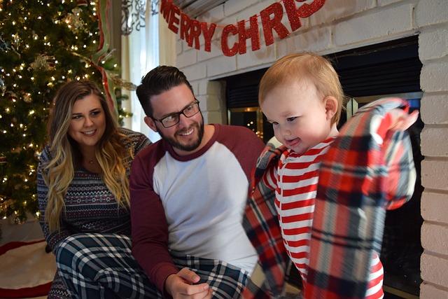 rodina o Vánocích, žena, muž a dítě si zkouší mikinu, za nimi krb, stromeček, a nápis merry christmas