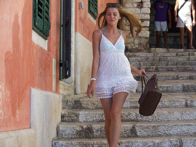 dívka v bílých šatech s kabelkou